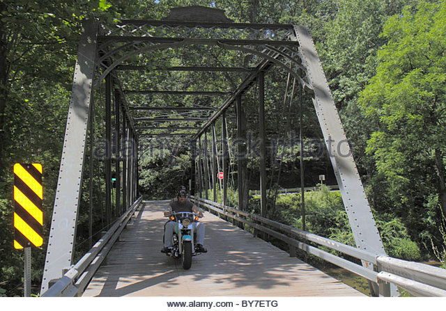 Maryland Harford County Street Cherry Hill Road over Deer Creek through truss bridge forest motorcycle bike man - Stock Image