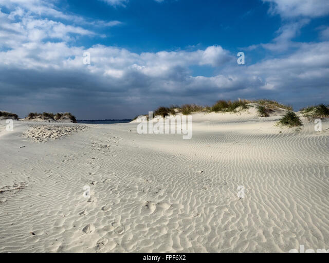 Footsteps in the sand by a dune at East Head, West Wittering, West Sussex - Stock Image
