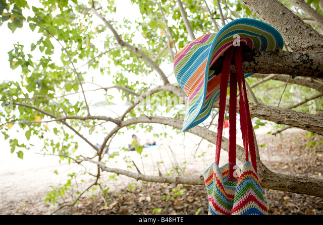 A beach hat and beach bag hang on the trees surrounding Leinster Bay, St. John, USVI. - Stock Image