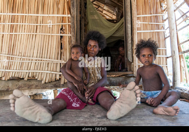 Local woman with children by her house Kuiawa, Papua New Guinea - Stock-Bilder