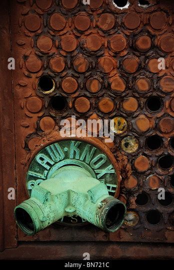 A corroded verdigreed pipe protrudes from a wall with an interested circular pattern with holes in it. - Stock Image