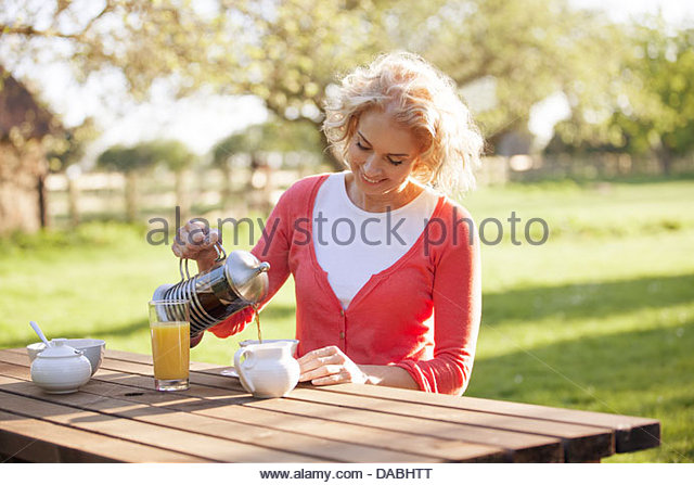 A mature woman sitting at a garden bench pouring coffee - Stock Image