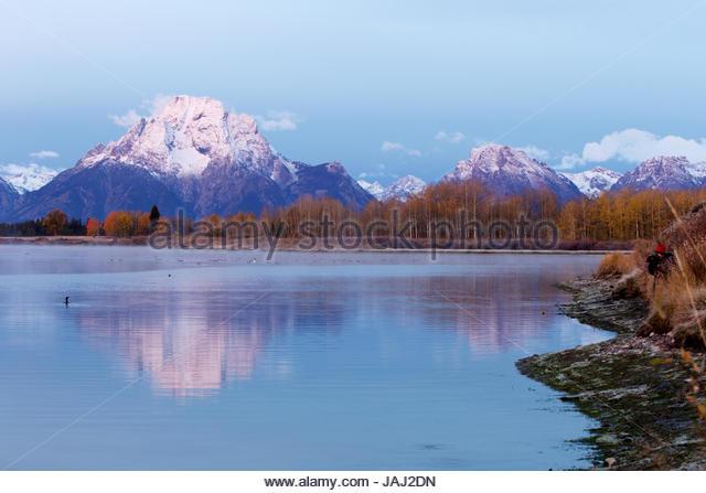 At sunrise a photographer surveys the Teton Range and Snake River in the Grand Teton National Park. - Stock Image