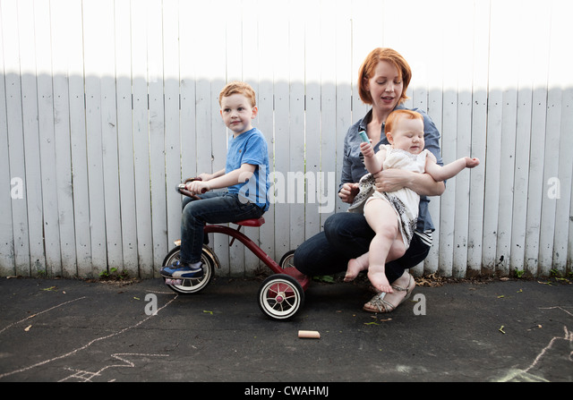 Mother playing in yard with two children - Stock-Bilder