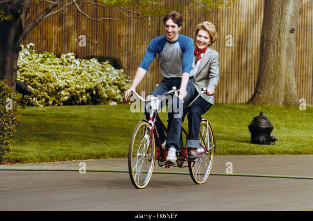 First Lady Nancy Reagan riding a tandem bicycle with son Ron Reagan on the south grounds of the White House April - Stock Image
