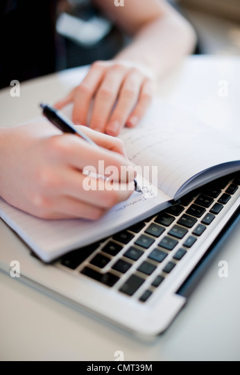 Woman writing in notepad while keeping it on keyboard - Stock Image