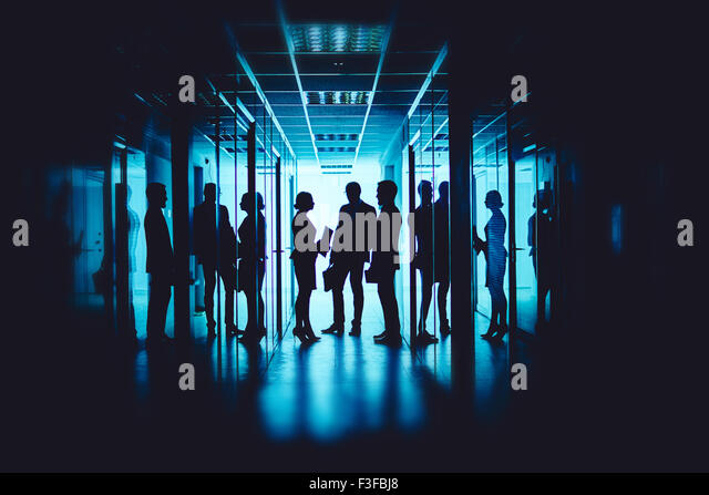 Group of co-workers interacting at meeting in corridor of business center - Stock Image