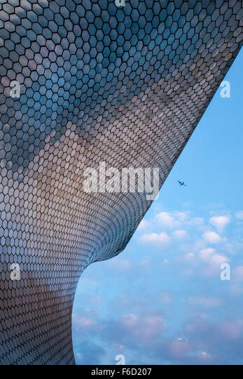 Airplane flies over the modern Soumaya Art Museum of Art in Mexico City, Mexico. - Stock Image