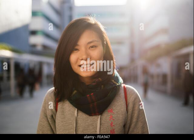 Portrait of young woman wearing hooded top and scarf, looking at camera smiling - Stock Image