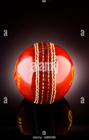 Red Leather cricket ball on shiny black background with reflection - Stock Image