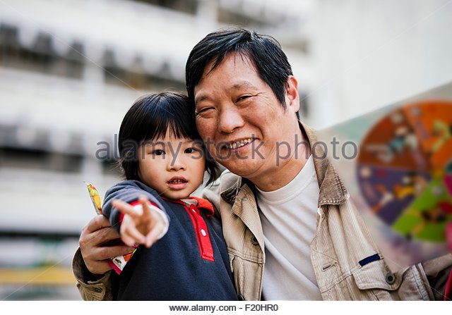 Portrait of mature man with arm around boy doing peace sign smiling - Stock-Bilder
