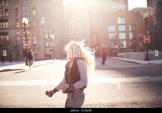 Young woman walking down street in Boston, carrying camera and smartphone - Stock Image