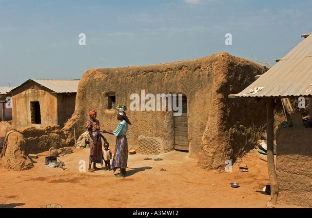 Village women with child Larabanga Ghana showing vernacular architecture with patterned mud walls - Stock Image