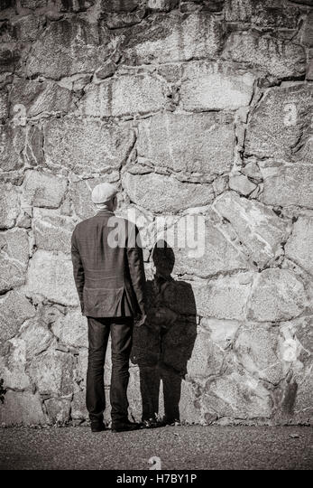 Old man standing in front of stone wall. Sunshine and heavy shadow. Building exterior with copy space. - Stock-Bilder