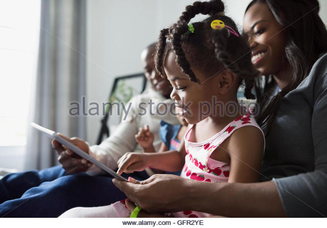 Young family using digital tablet - Stock Image