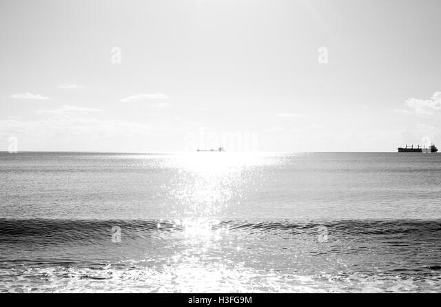 Two freight ships on the horizon, one bathed in sunlight - Stock Image