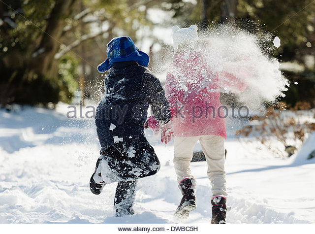 Two children running in snow - Stock Image