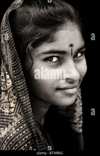 Happy young Indian teenage girl wearing traditional silk sari portrait. Sepia Tone - Stock Image