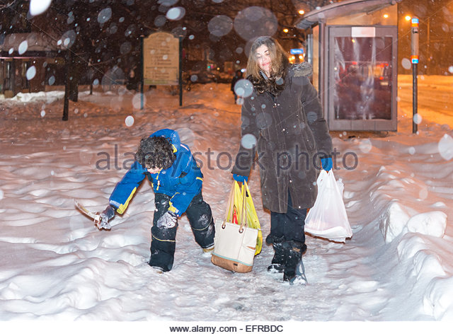 Everyday life of a single mother in Toronto during Winter, after work she picks up her kid,buys groceries and return - Stock-Bilder