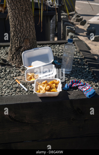 Leftover fish and chips, discarded electronic cigarette on seafront, Barmouth, North Wales - Stock Image