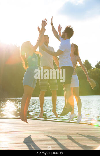 Four friends high fiving at a lake in backlight - Stock Image