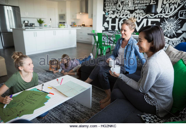 Mothers drinking coffee and daughters coloring enjoying play date in living room - Stock Image