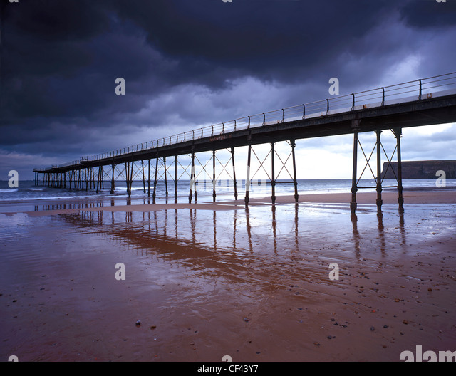 Saltburn Pier, the last pier remaining in Yorkshire, at low tide as storm clouds gather overhead. - Stock Image