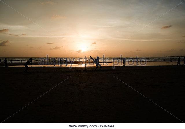 People playing cricket on mumbai beach - Stock Image