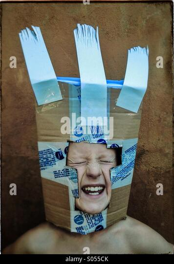 Boy playing with a carton box mask - Stock Image