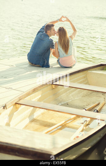 Couple in love sitting on the pier, their hands show heart - Stock Image