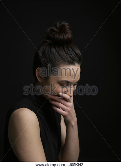 Laughing brunette woman covering mouth and looking down against black background - Stock Image