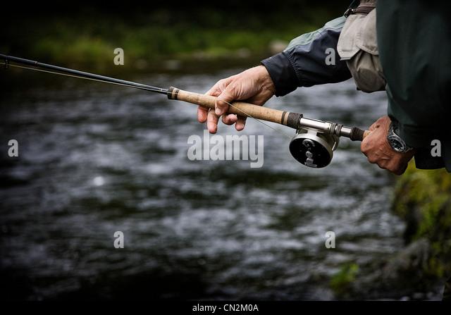 Casting fishing rod in Margaree River, Cape Breton Island, Nova Scotia - Stock Image