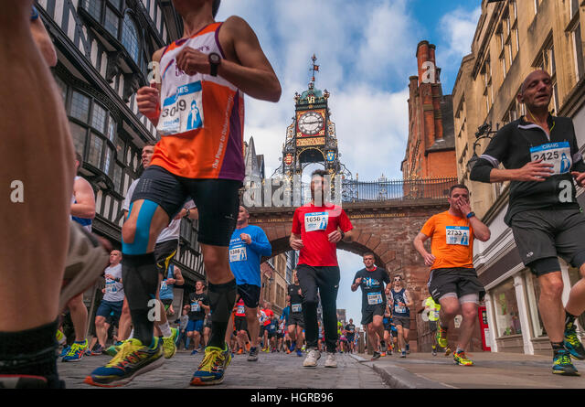 Marathon runners pass under the Eastgate clock bridge in Chester . North West England. - Stock Image