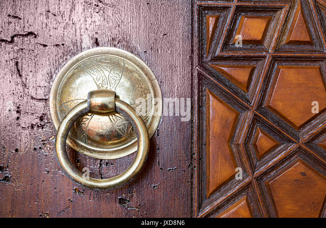 Closeup of antique copper ornate door knocker over an aged wooden door, Suleymaniye Mosque, Istanbul, Turkey - Stock Image