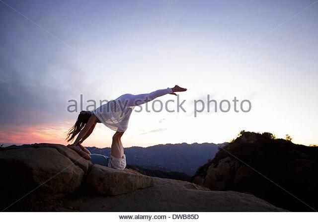 Couple in gymnastic pose, on Topanga Canyon at sunset - Stock-Bilder