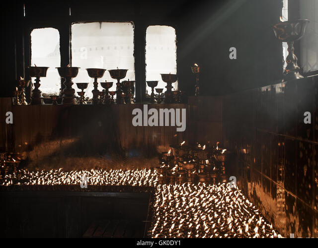 Candles burning in the Boudhanath Stupa in Nepal - Stock Image