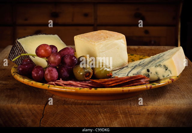 Small antipasti platter of mostly Italian cheeses and meats with olives and grapes - Stock Image