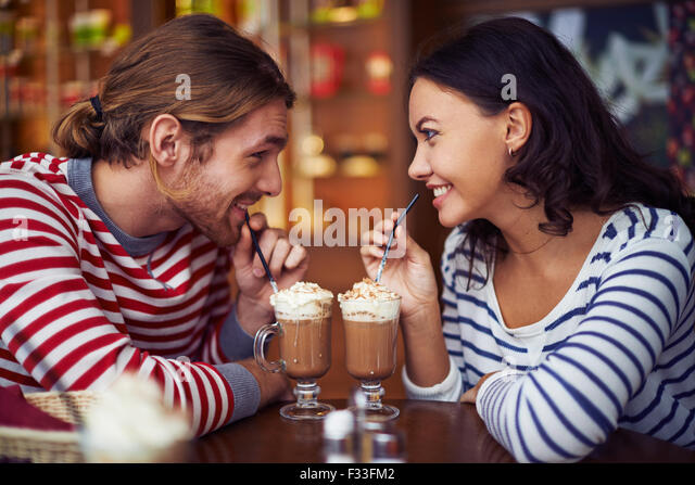 Happy young dates having latte during rest in cafe - Stock Image