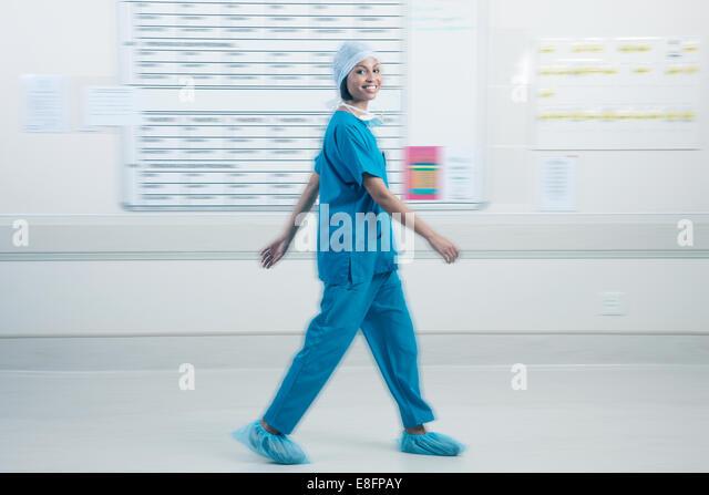 Doctor walking past schedule board in hospital - Stock-Bilder