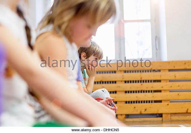 Children sitting on bench in school hall, looking sad - Stock Image