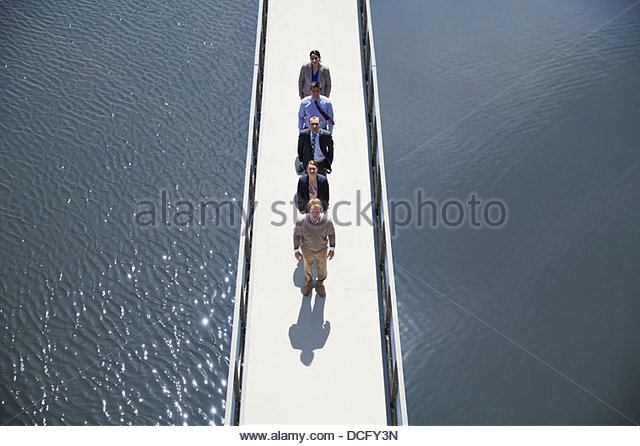 Business people standing in a row on a bridge - Stock Image