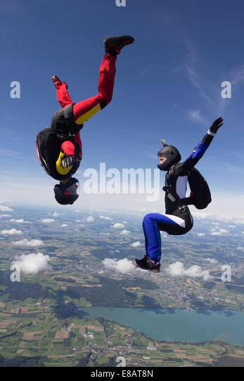Team of two female skydivers in sit fly and head down positions over Buttwil, Luzern, Switzerland - Stock-Bilder
