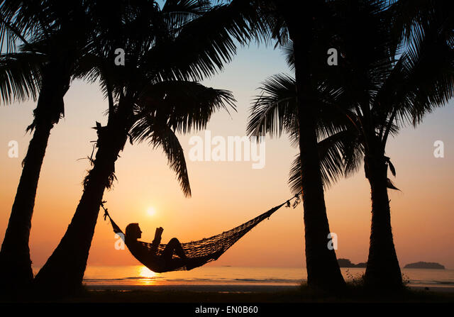 beach vacations, silhouette of woman reading in hammock - Stock Image