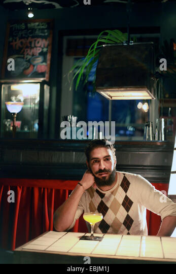 Man with cocktail at bar - Stock Image