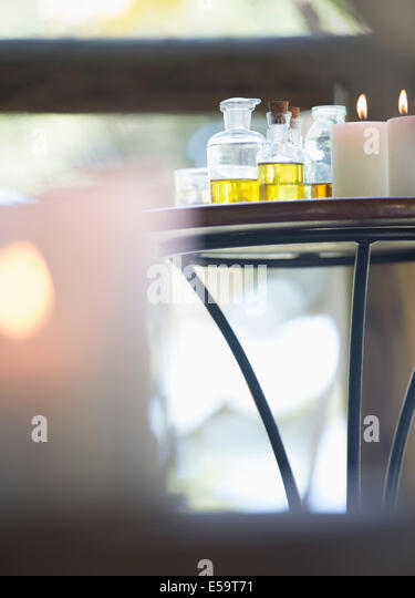 Essential oils and candles on table - Stock Image