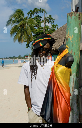 Jamaica Negril beach cool Rastafari man in front of fashion shop - Stock Image