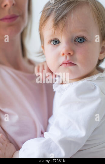 Close up of a young girl in her mother's arms. - Stock Image