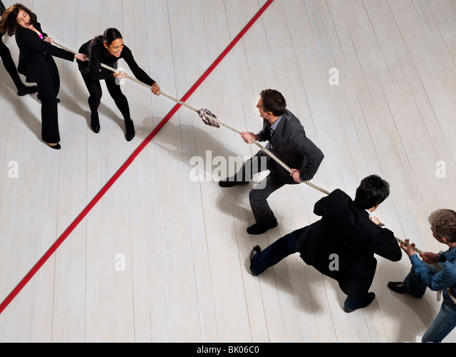 Business people playing tug of war - Stock Image