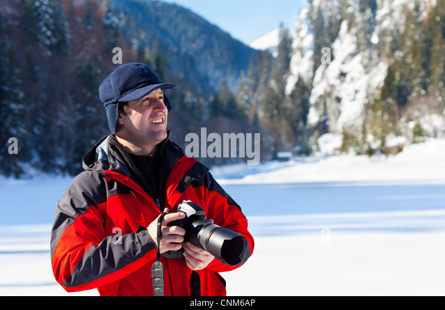 Portrait of a professional nature photographer outdoor in the winter landscape - Stock Image