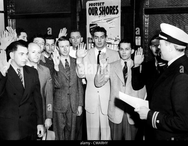 Victor Mature (center), American film actor, enlisting in the Coast Guard, National Airport, Virginia, 1943.. Courtesy: - Stock-Bilder